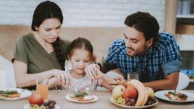Il padre e madre insegna alla bambina mangia la coltelleria fotografia stock libera da diritti