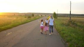 Il padre e madre maturo felice con tre bambini va sulla strada in campagna sul tramonto La famiglia felice si diverte sulla natur stock footage