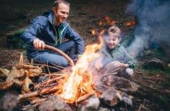 Il padre ed il figlio fanno il falò nel viaggio di campeggio della foresta alla molla o fotografia stock