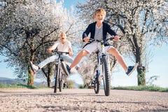 Il padre ed il figlio hanno un divertimento quando guida le biciclette sulla strada campestre w Fotografia Stock Libera da Diritti