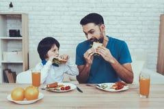Il padre ed il figlio hanno una prima colazione fotografia stock