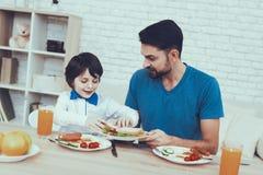 Il padre ed il figlio hanno una prima colazione immagini stock libere da diritti