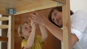 Il padre ed il figlio montano la mobilia di legno dalle piccole parti Il ragazzino aiuta suo padre a montare una tavola stock footage