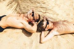 Il padre ed il figlio si trovano sulla sabbia nell'ombra della palma Isl tropicale Fotografia Stock