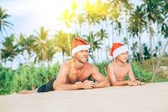 Il padre ed il figlio sorridenti felici in cappelli di Santa hanno bagno del sole sulla spiaggia sabbiosa dell'isola fotografia stock