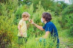 Il padre ed il figlio usano uno spruzzo da un'allergia a causa di un'allergia all'ambrosia Immagine Stock Libera da Diritti
