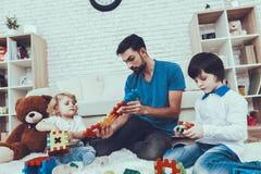 Il padre ed i figli sta giocando con i giocattoli fotografia stock