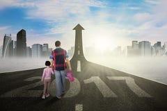 Il padre ed il bambino camminano verso la freccia con 2017 Fotografie Stock