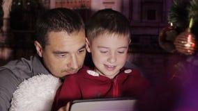 Il padre ed il figlio all'albero di Natale giocano sulla compressa video d archivio