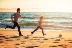 Il padre ed il figlio felici giocano a calcio o calcio sopra fotografia stock libera da diritti