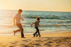 Il padre ed il figlio felici giocano a calcio o calcio sopra Fotografie Stock