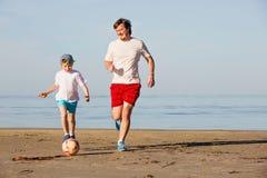 Il padre ed il figlio felici giocano a calcio o calcio sopra Fotografia Stock
