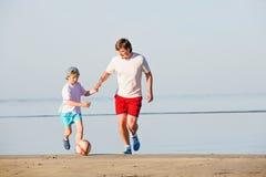Il padre ed il figlio felici giocano a calcio o calcio sopra Fotografie Stock Libere da Diritti