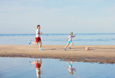 Il padre ed il figlio felici giocano a calcio o calcio sopra immagini stock libere da diritti