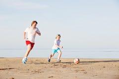 Il padre ed il figlio felici giocano a calcio o calcio sopra Immagini Stock