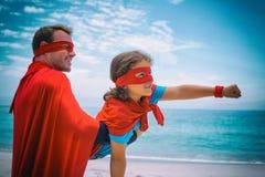 Il padre ed il figlio felici nel supereroe costume godere alla spiaggia royalty illustrazione gratis