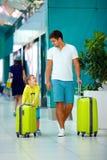 Il padre ed il figlio felici sono pronti per l'imbarco nell'aeroporto internazionale Fotografie Stock
