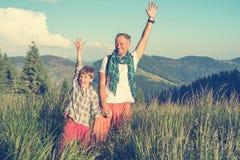 Il padre ed il figlio felici stanno stando nel prato alpino, stretchi Immagini Stock