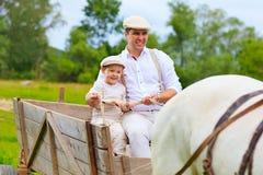 Il padre ed il figlio guidano un carretto del cavallo Fotografie Stock