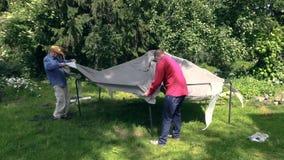 Il padre ed il figlio hanno messo il panno della tenda sulla costruzione del tetto di capanna del giardino Immagine Stock Libera da Diritti