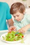 Il padre ed il figlio producono il condimento dell'insalata Fotografia Stock