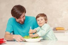 Il padre ed il figlio producono il condimento dell'insalata Immagine Stock