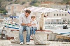 Il padre ed il figlio si siede con i cani su un banco vicino al mare fotografia stock libera da diritti
