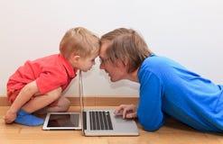 Il padre ed il figlio sono in conflitto sopra il cuscinetto ed il computer di tocco Fotografie Stock Libere da Diritti