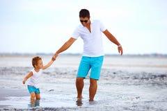 Il padre ed il figlio superano insieme gli ostacoli, estuario salato immagini stock
