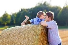 Il padre ed il piccolo figlio che si divertono sul fieno giallo sistemano di estate Fotografie Stock