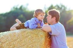 Il padre ed il piccolo figlio che si divertono sul fieno giallo sistemano di estate Fotografie Stock Libere da Diritti