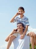 Il padre ed il suo figlio stanno parlando sopra i mobiles fotografia stock libera da diritti