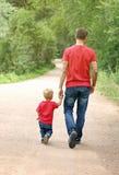 Il padre ed il suo ragazzo del bambino stanno camminando nel parco, tenentesi per mano Concetto di paternità Abbigliamento di sgu Fotografia Stock