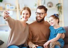 Il padre felice allegro ed il bambino della madre della famiglia prendono i selfies, prendono le immagini immagini stock