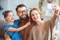 Il padre felice allegro ed il bambino della madre della famiglia prendono i selfies, prendono le immagini fotografie stock