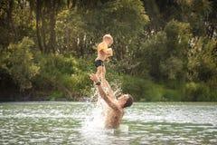 Il padre felice che gioca il bambino del figlio getta la paternità e l'infanzia felici su di nuoto di concetto del ritratto di st immagini stock