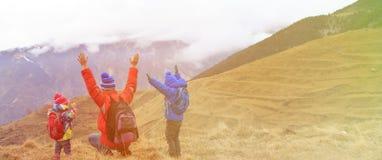 Il padre felice con due bambini viaggia in montagne sceniche Fotografie Stock