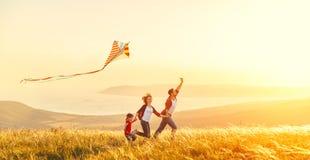 Il padre felice della famiglia della figlia del bambino e della madre lancia un aquilone o Fotografia Stock