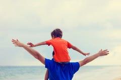 Il padre felice ed il figlio che giocano sul mare tirano Immagini Stock Libere da Diritti