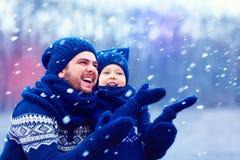 Il padre felice ed il figlio che si divertono al di sotto dell'inverno nevicano, ferie Fotografia Stock