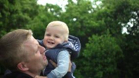 Il padre felice gioca con il figlio sveglio di un anno in foresta archivi video