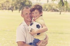 Il padre felice giovane che continua la sua parte posteriore ha eccitato 7 o 8 anni del figlio che gioca insieme il calcio di cal Fotografie Stock