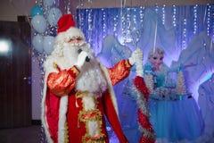 Il padre Frost parla con un microfono Santa Claus sta cantando le canzoni di Natale contro Uomo nel vestito di Santa Claus che po fotografie stock libere da diritti