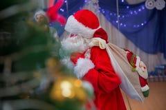 Il padre Frost parla con un microfono Santa Claus sta cantando le canzoni di Natale contro Uomo nella posa del vestito di Santa C immagini stock libere da diritti
