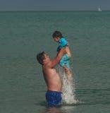 Il padre getta la figlia dell'acqua fotografia stock