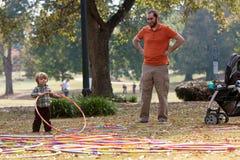 Il padre guarda il gioco del figlio del bambino con i cerchi di Hula immagini stock
