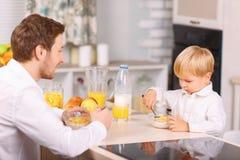 Il padre guarda suo figlio mangiare i fiocchi di granturco Fotografie Stock