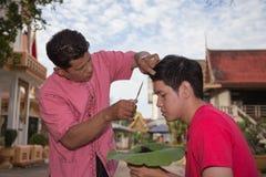 Il padre ha tagliato i capelli del figlio nella cerimonia buddista di classificazione Immagine Stock