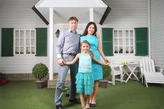 Il padre, la madre e la figlia sorridenti stanno il portico vicino Immagine Stock