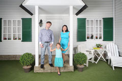 Il padre, la madre e la figlia stanno il portico vicino Fotografia Stock